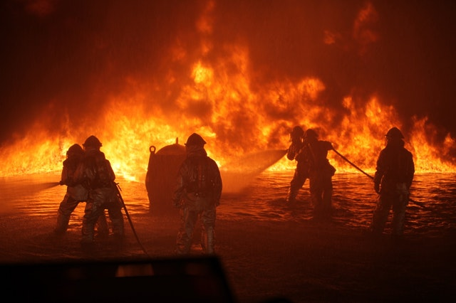 firefightes in front of raging wildfire
